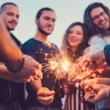 Happy friends holding burning sparklers on rooftop party
